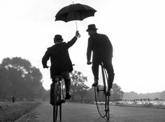 old photo of 2 men riding bikes