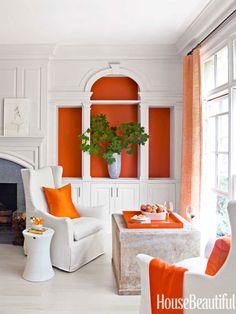 In the living room of a Atlanta, Georgia, house, orange paint sets off the Palladian details of the bookcase.