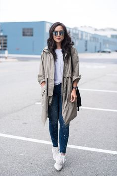 A parka layered over a tee, distressed skinny jeans, and sneakers.
