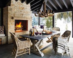 The covered porch of this Idaho home is paved in gray sandstone tiles with a driftwood chandelier from Mecox Gardens. The limestone fireplace is flanked by seating areas covered with Holly Hunt fabric cushions. The porch serves as an open-air dining pavilion with views of the Sawtooth Mountains.  Tour the entire home.
