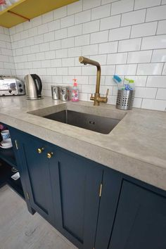 Detail of bespoke polished concrete worktops reclaimed brass handles farrow and ball paints