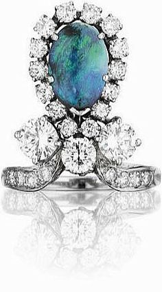 Designed as a tear-drop shaped ring, centering on a row of three circular-cut diamonds, set with an oval-cut cabochon opal within a circular-cut diamond surround, to the circular-cut diamond half hoop, mounted in platinum. by Phillips
