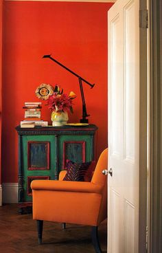 """Too Hot to Handle. Eclectic Style living room with Persimmon Orange walls, Tangerine Orange chair and painted cabinet in Hunter and Kelly green featured in Tricia Guild's book """"In Town"""" Orange Rooms, Living Room Orange, Orange Walls, Orange Room Decor, Tricia Guild, Orange Interior, Interior Decorating, Interior Design, Decorating Ideas"""