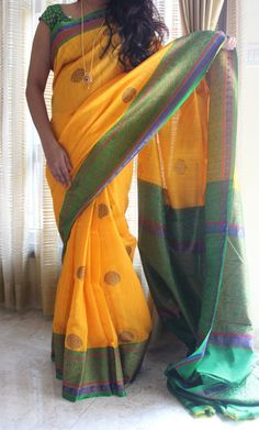 A rich yellow coloured banaras silk saree with gold motifs on the body and double side rich green border. Comes with an attached green blouse.
