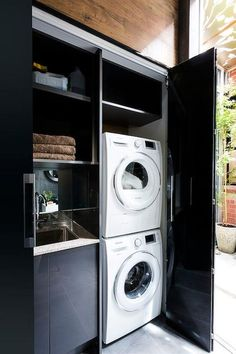 Glossy black double doors open to a closet filled with white stacked washer and dryer next to black cabinets fitted with a sink under black shelves.