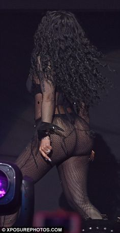 Derriere on display! The outspoken rapper made sure her world-famous curves were on full display as she took to the stage in just a thong and fishnet bodysuit