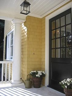 """""""A black door adds sophistication to a mustard yellow home."""" hmmmmm...."""