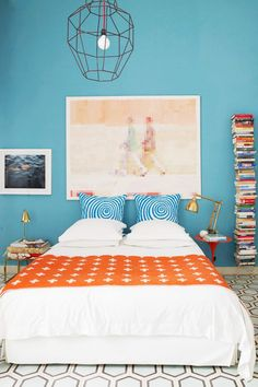 Bright blue bedroom with vintage tiled floors, a large metal pendant light