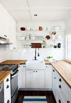 Compacte witte keuken in landelijke stijl met houten werkblad.