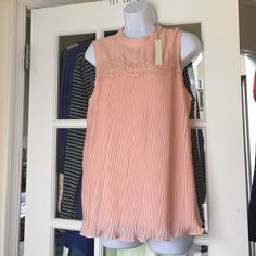 LC Lauren Conrad Rose Sleeveless Pleated Top Color : Antique Rose. Size : Large . Blouse is a rose color, but looks peachy. Soft and pretty. 100% polyester. Blouse front has lace yoke with pleats. One button on the back neck for closure. Brand new with tags. LC Lauren Conrad Tops Blouses