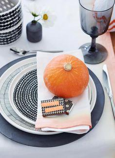 Tischset mit verschiedenen Tellern und einem Kürbis