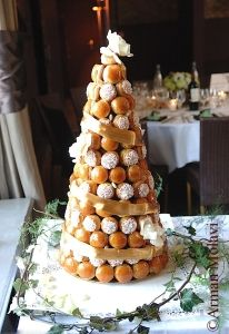 """The croquembouche is a tower of creme-filled, puff-pastry balls (called """"choux"""" in French) which are piled into a high pyramid and encircled with caramelized sugar."""