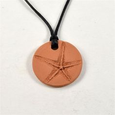 This essential oil diffuser pendant necklace was made by hand using a natural red earthenware clay. The pendant has the imprint of a real starfishon the front and is left unglazed for a natural, organic look. It was fired in the kiln to over 1900 degrees. The pendant is approx. 1 7/16. It comes with a black satin cord necklace with adjustable sliding knots. Just drop 1-3 drops of essential oil onto the pendant and wait 1-2 minutes for it to absorb into the earthenware clay. Then wear you...