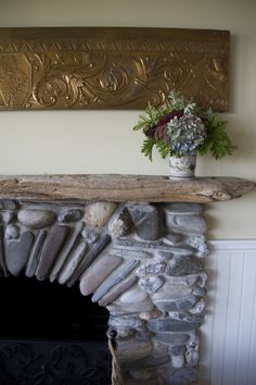 I found every rock for my fireplace on the beach near my house. The driftwood mantle, too. Antique bank sign above.