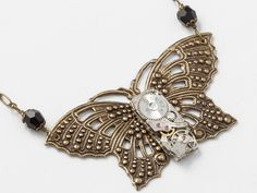 Steampunk jewelry necklace with a silver watch movement and gold filigree butterfly with black crystals #SteampunkNecklace  #SteampunkJewelry #SteampunkJewelrybyMariaSparks #butterfly
