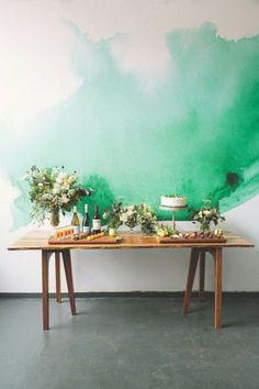 Une table de mariage devant un mur décoré avec de la couleur verte