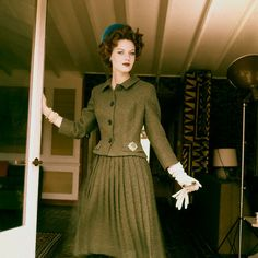 Model is wearing a green wool tweed suit, short fitted jacket with a long pleated skirt. Accented by bright blue velvet pillbox hat.