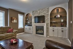 Stunning family room features high ceilings, stone wall, custom built-ins and gas fireplace with cast stone surround.