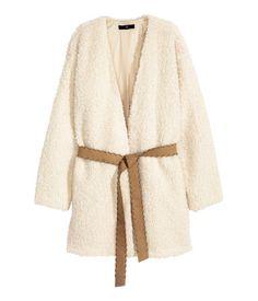 Weiß. Gerade geschnittene, offene Jacke aus Teddyfleece. Modell mit Bindegürtel aus Lederimitat und Nahttaschen. Gefüttert.