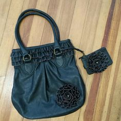 """Mud Pie Handbag W/ detachable Wristlet. Black with ruffle trim on top & round ruffled flower on bottom & on wristlet. Brown trim on flower & ruffle. Wristlet is detachable has zipper con part mentioned & slot w/ snap on back. Purse has 1 zipper & 2 open slots. 13 1/2"""" tall by q3"""" wide. Man made materials. Used only once. mud pie Bags"""