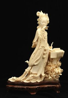 A fine Chinese ivory carving, of Li Qingzhao, a noted beauty and poet depicted standing by a table with a scroll, inkstone and brushes height: 13 in. (33 cm).