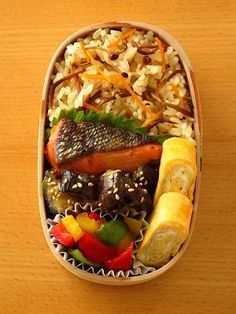 Bento box featuring grilled salmon, rice with carrot & burdock, miso-glazed eggplant, tamagoyaki, and colorful peppers