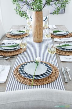 An Easter tablescape with a navy blue striped runner and navy and white gingham plates. Love the simplicity of this natural place setting!