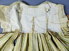 """Inside view, robe à la francaise, France, ca. 1760. """"Mexicaine"""" silk taffeta with yellow stripes on cream ground alternating with stripes with small bouquets on light blue and cream ground, linen lining. Sleeve ruffles with pink trimmings."""