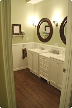 love the green, white and brown in this bathroom, and the round framed mirrors.