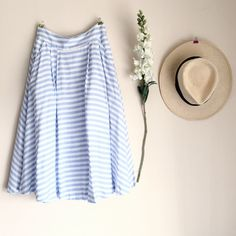 """HP 1/22. Joa Midi Skirt Super cute, worn once, like new!!  When a skirt as cute as the JOA All Striped Up Ivory and Light Blue Striped Midi Skirt comes along, you better believe the hype!   Woven ivory & light blue stripes Banded waist  Midi length skirt  Pleats Pockets  A satiny woven lining transitions into tulle towards the hem to offer extra volume.   Hidden back zipper/hook clasp.  Lined.  Model is 5'7"""" and is wearing a size small.  Self: 100% Rayon.  Lining 1: 100% Polyester.  Lining…"""