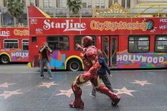 A tourist snaps a man dressed as Ironman on Hollywood Boulevard, California.
