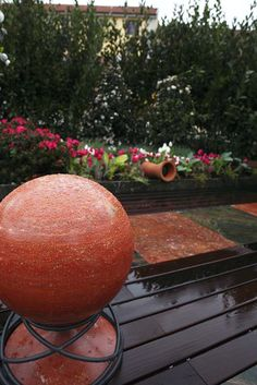 Red travertine Sphere and terracotta Yo-yo sound modules by Architettura Sonora.  Private terrace, Milano.
