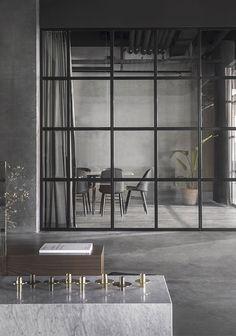 Espacio estilo nórdico tipo loft, cerramiento de hierro y cristal, color gris y suelo de cemento