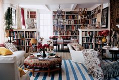 Inside Carolina Irving's prewar Manhattan apartment, the library and living room features a blue and white dhurrie from Jaipur, a Robert Kime pouf, and a first-century A.D. Celtic stone head.