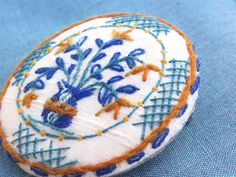 Delftware ceramic plate style brooch in crewelwork hand embroidery on silk.  Inspired by the amazing colours in antique English delftware