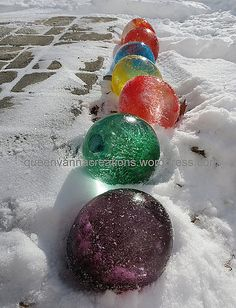 Fill a balloon up with water, add food coloring, then freeze it outdoors when it's cold. Remove the balloon and you'll have these cool colored ice balls!