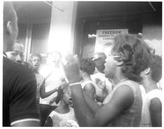 Local African-American teenagers sing and clap their hands in front of Freedom Summer headquarters at 507 Mobile Street. The young woman in the striped top is Barbara Ann Johnson. In the foreground is Bessie Houze. Herbert Randall, USM archive