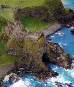 Aerial view showing the medieval ruins of Dunluce Castle resting on top of Mermaids Cave in Northern Ireland.