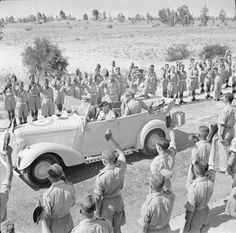 HM King George VI rides with General Montgomery in a staff car between lines of cheering troops during his first visit to Tripoli, 21 June 1943
