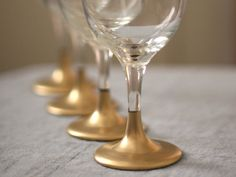DIY: Gold Dipped Glasses  - These are gorgeous.  You can find these glasses for about a buck, or less, a piece.  Grab a can of metallic spray paint (any color) and there you go!  Instant glamour!