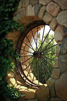 repurosed wagon wheel as window feature in garden