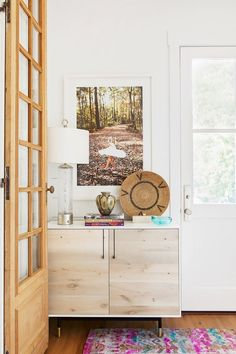 The white shiplap walls with bright colors and a whitewashed dresser
