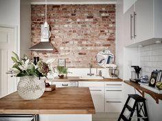 Czerwone cegły podkreślają wyjątkowość kuchni w stylu skandynawskim. Białe proste szafki kuchenne i drewniane blaty...