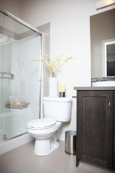 Main bathroom with dark shaker style maple cabinets, glass mosaic tile backsplash and cream walls. Glass shower door highlighted with white and yellow accents. At Prospect Rise townhomes by Avi Urban