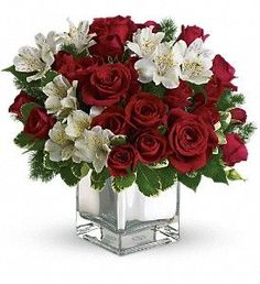 "Have yourself a modern little Christmas with red roses and white alstroemeria in a charmingly contemporary silver cube. After the holidays, you can use the vase to add pizzazz to bouquets year-round.  The stylish Christmas flower arrangement includes red roses, red spray roses and white alstroemeria accented with pittosporum and ming fern.  Approximately 11 1/2"" W x 12"" H  Orientation: All-Around  As Shown : T407-3A Deluxe : T407-3B Premium : T407-3C"