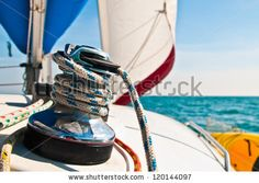 stock photo : Horizontal photograph of a blue and white line wrapped around a large metal winch with white and red sail set in background.