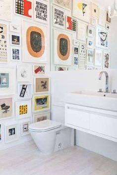 decoração de banheiro lavabo com muitos qradros, gallery wall no banheiro lavabo, banheiro moderno, quadros com ilustrações coloridas no banheiro