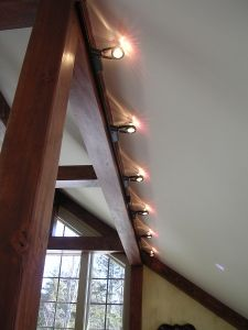 Small halogen track lighting is useful as it can be hidden by a beam yet project optimal lighting.
