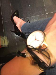 Gold watch, black shoes, ripped jeans, bracelets