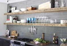 reclaimed wood shelves.  grey subway tile wall.  awesome. hanging knives over oven, good space saver